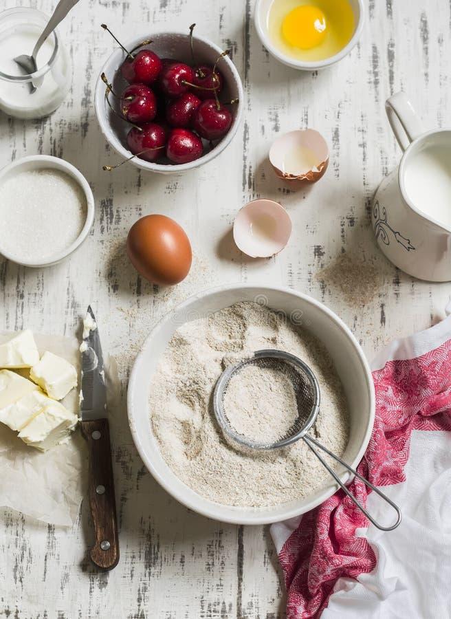 Baksel rustieke lichte achtergrond Ruwe ingrediënten voor bakselpastei met kersen - bloem, eieren, melk, suiker, boter, room, ker stock afbeelding