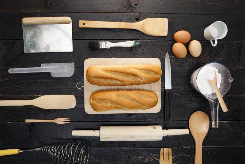 Bakselachtergrond met brood, bloem, deegrol, eieren, houten spo royalty-vrije stock fotografie