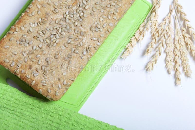 Bakselbrood thuis Een brood van vers gebakken wholegrain brood met zonnebloemzaden ligt op een scherpe raad Nabijgelegen leugens  royalty-vrije stock foto