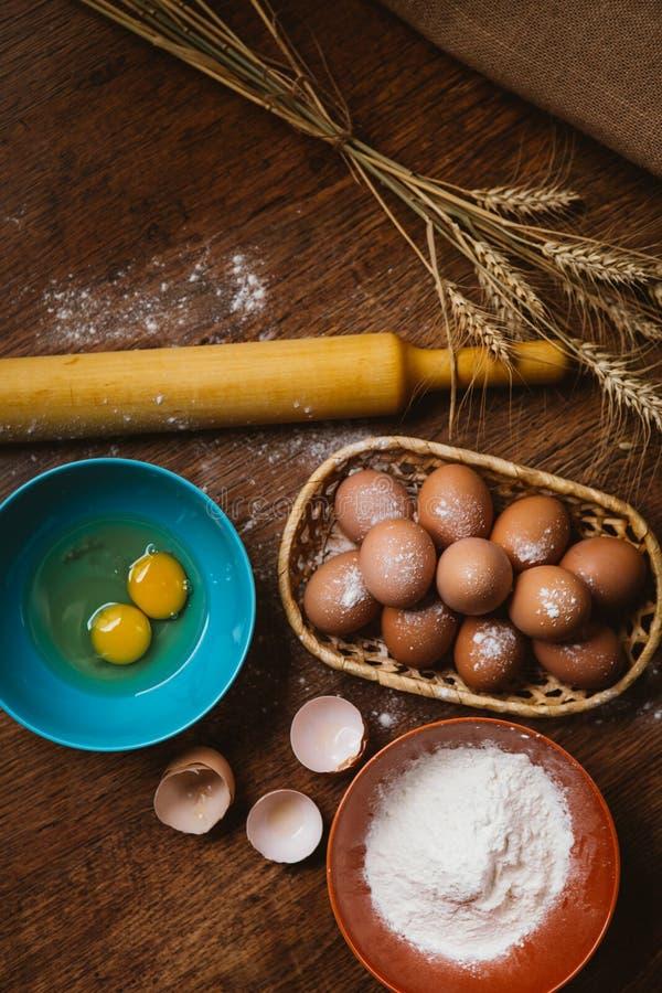 Bakselcake in landelijke keuken - de ingrediënteneieren van het deegrecept, bloem, suiker op uitstekende houten lijst van hierbov stock afbeeldingen