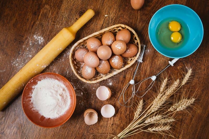 Bakselcake in landelijke keuken - de ingrediënteneieren van het deegrecept, bloem, suiker op uitstekende houten lijst van hierbov stock afbeelding