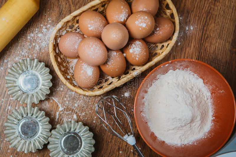 Bakselcake in landelijke keuken - de ingrediënteneieren van het deegrecept, bloem, suiker op uitstekende houten lijst van hierbov royalty-vrije stock afbeeldingen