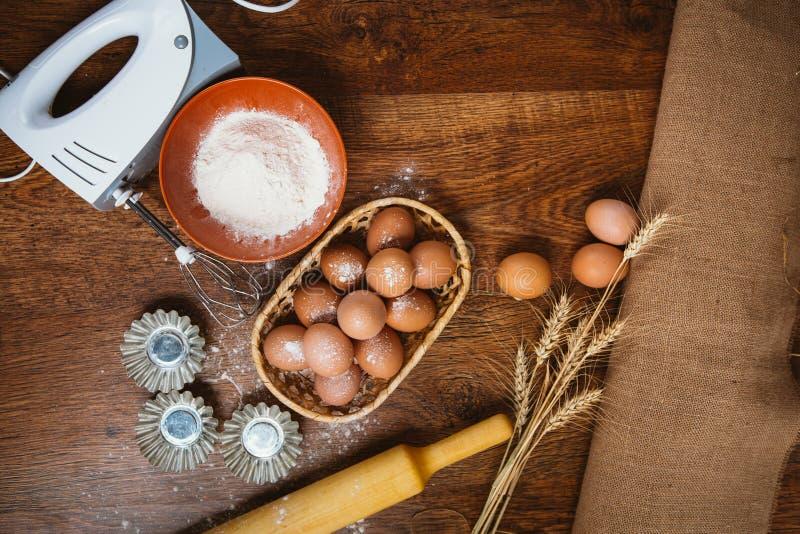 Bakselcake in landelijke keuken - de ingrediënteneieren van het deegrecept, bloem, suiker op uitstekende houten lijst van hierbov stock foto