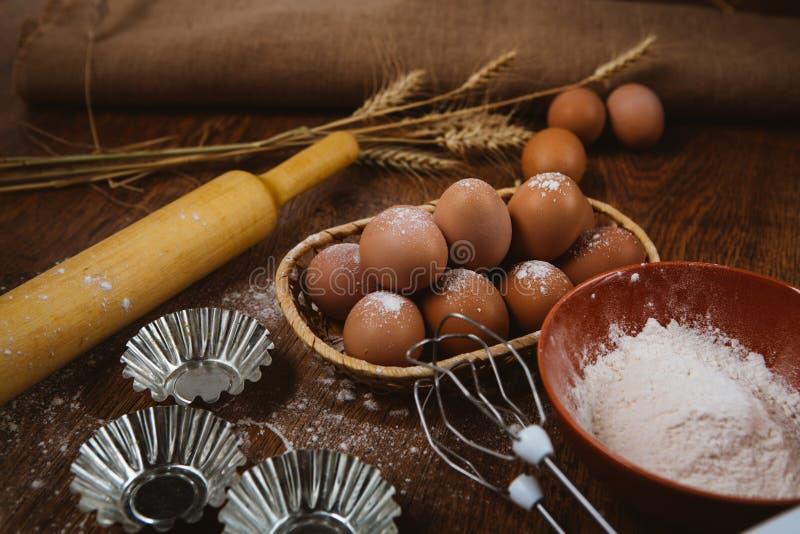 Bakselcake in landelijke keuken - de ingrediënteneieren van het deegrecept, bloem, suiker op uitstekende houten lijst van hierbov royalty-vrije stock afbeelding