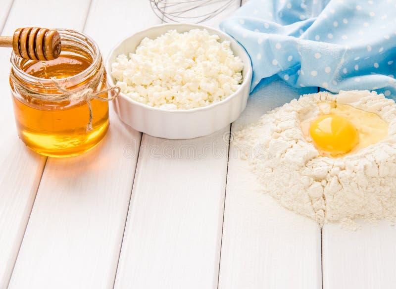 Bakselcake in rustieke keuken - de de ingrediënteneieren van het deegrecept, bloem, melk, boter, honing op wit planked hierboven  royalty-vrije stock afbeelding