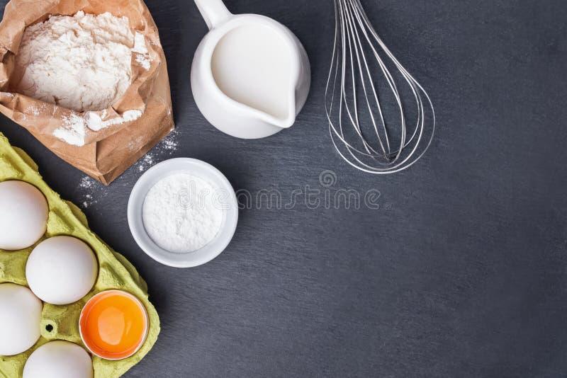 Bakselingrediënten en hulpmiddelen op de zwarte steenachtergrond stock afbeelding