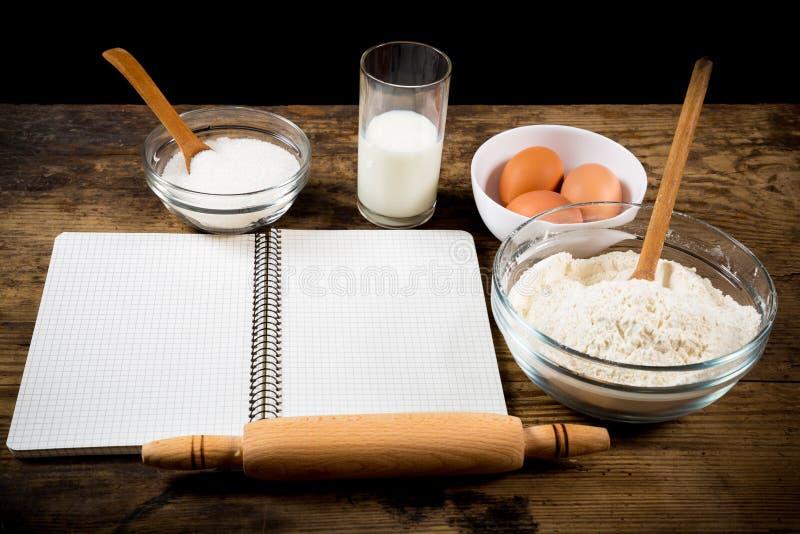 Bakselingrediënten en kokboek op lijst royalty-vrije stock afbeelding