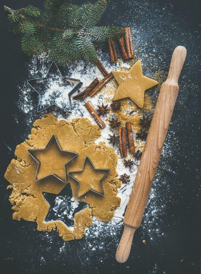 Bakselingrediënten voor voorbereiding van de peperkoekkoekjes van de Kerstmisvakantie de traditionele, zwarte achtergrond stock afbeeldingen