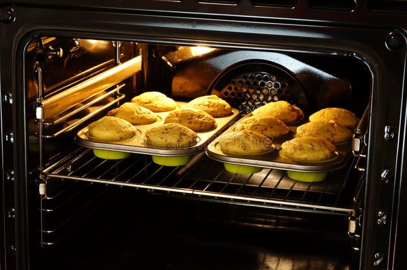 Bakselmuffins in oven stock afbeelding