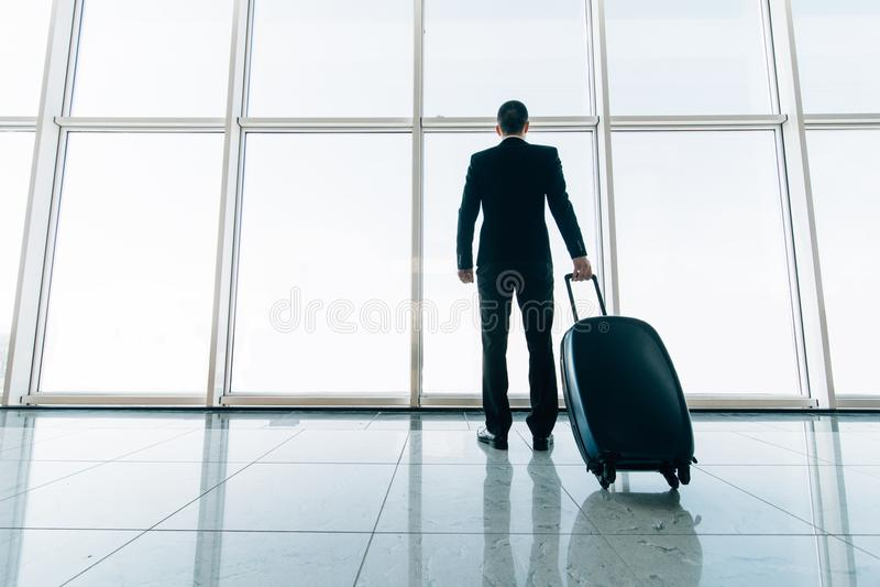 Baksida av affärsmannen och resväskan i det väntande på flyget för flygplats Resa begreppet, begreppet för sommarsemestern, hande royaltyfri foto