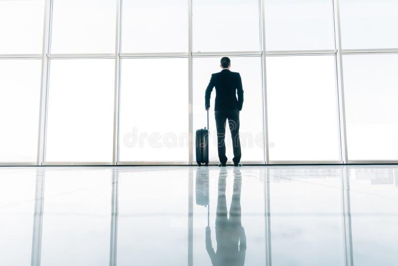 Baksida av affärsmannen och resväskan i det väntande på flyget för flygplats Resa begreppet, begreppet för sommarsemestern, hande royaltyfri fotografi