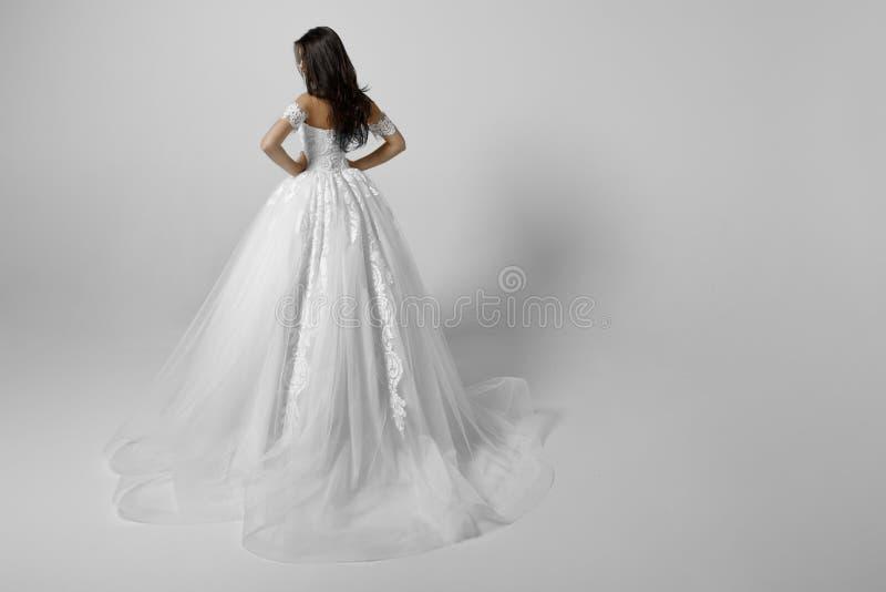 Baksida av att charma den unga bruden i lyxig bröllopsklänning Nätt flicka i den vita prinsessaklänningen, på vit bakgrund arkivfoton