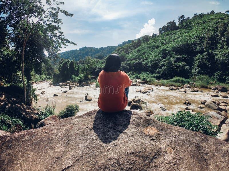 Baksida av den asiatiska kvinnan som sitter av stort, vaggar överst på vattenström a arkivbilder