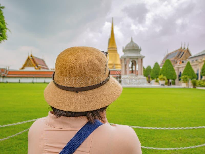 Baksida av den höga turisten i Wat Phrakeaw Temple med molnhimmel fotografering för bildbyråer