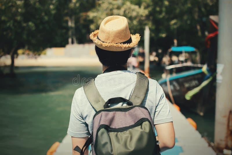 Baksida av den unga för man som handelsresanden solo går på banan in mot den tropiska ön i Thailand royaltyfri foto