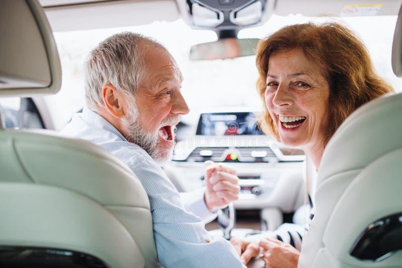 Baksida av ett lyckligt högt par som sitter i bil och ser tillbaka arkivbilder