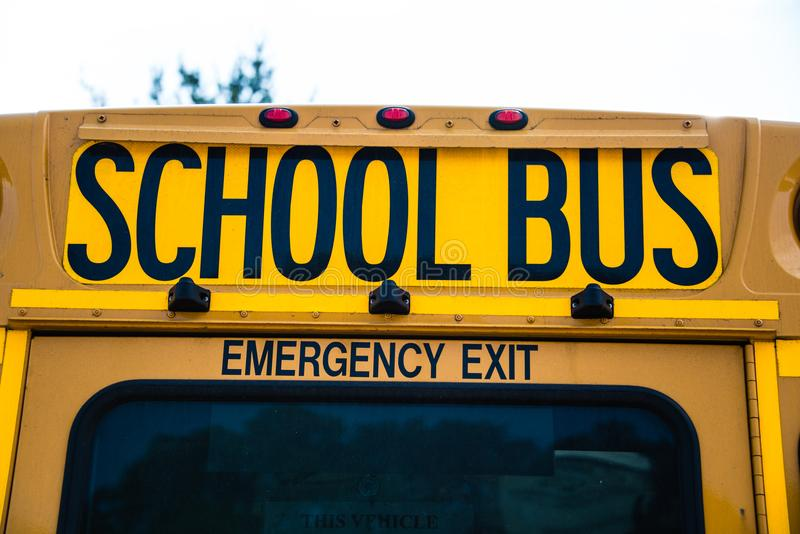 Baksida av USA-skolbussen som visar den nöd- utgången royaltyfri foto