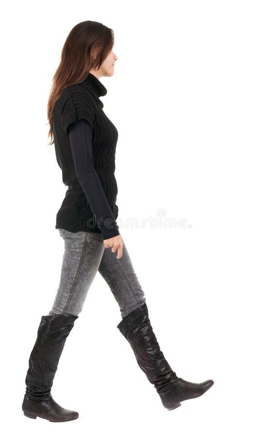 Baksida beskådar av gående kvinna i jeans och tröja royaltyfria bilder