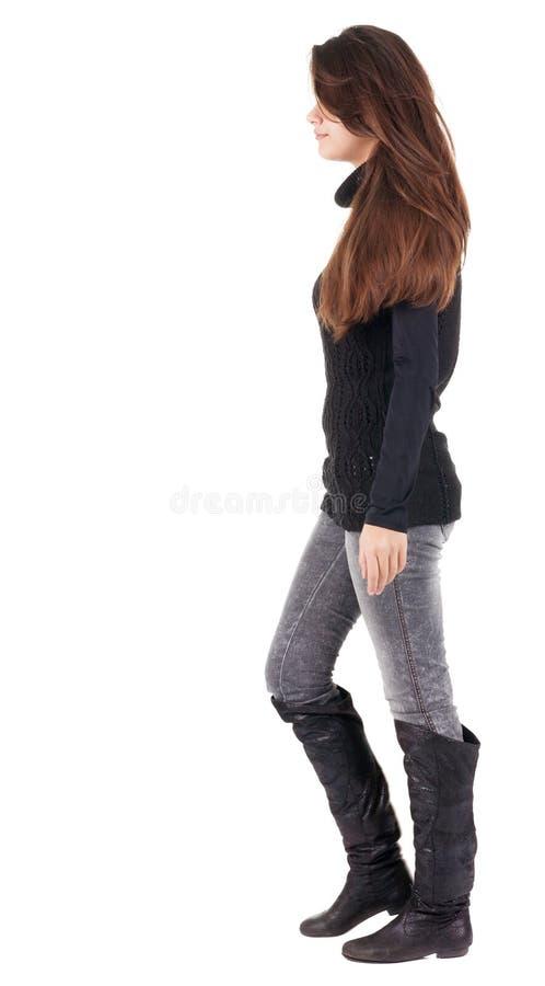 Baksida beskådar av gående kvinna i jeans och tröja royaltyfri bild