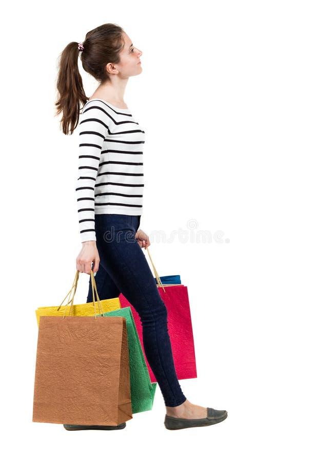 Baksida beskådar av gående kvinna med shopping hänger lös härlig flicka mig royaltyfri bild
