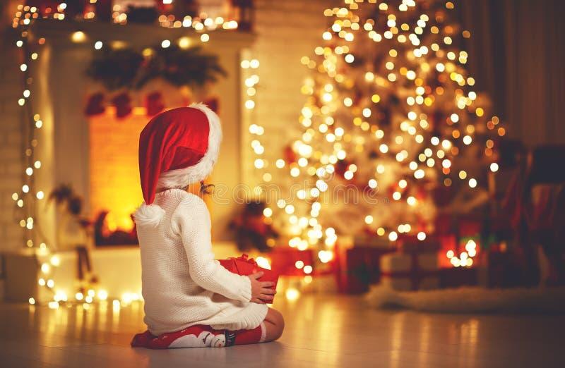 Baksida för barnflickasammanträde framme av julgranen på Christm fotografering för bildbyråer