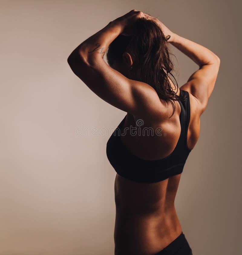 Baksida för kvinnlig visning för kondition muskulös