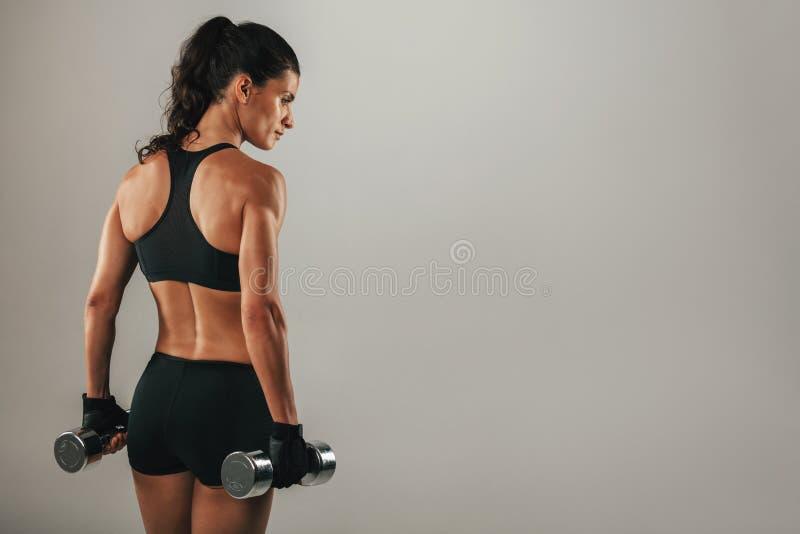 Baksida sikt för tre fjärdedel av den kvinnliga kroppsbyggaren fotografering för bildbyråer