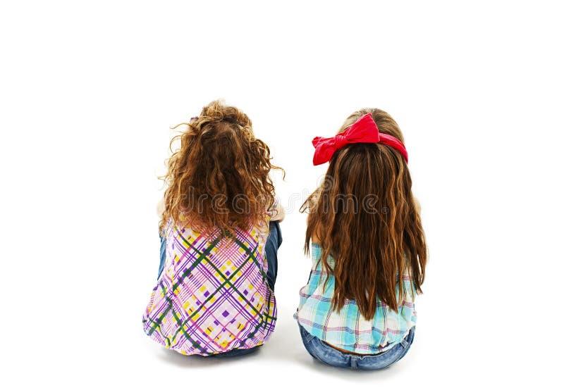 Baksidaen beskådar av liten flicka två som sammanträde däckar på och se upp arkivbilder
