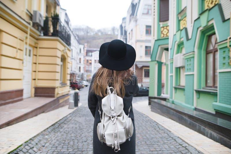 Baksidan är en stilfull kvinna som strosar längs gatorna av en härlig gammal stad royaltyfria bilder