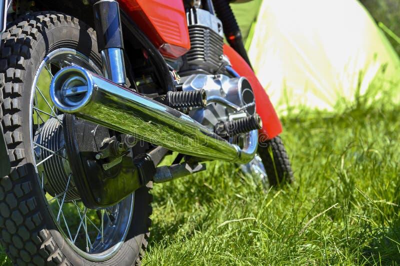 Baksidan av den r?da motorcykeln p? bakgrunden av ett turist- t?lt Begreppet av stil av liv p? hjul: v?gen och hastigheten royaltyfri bild