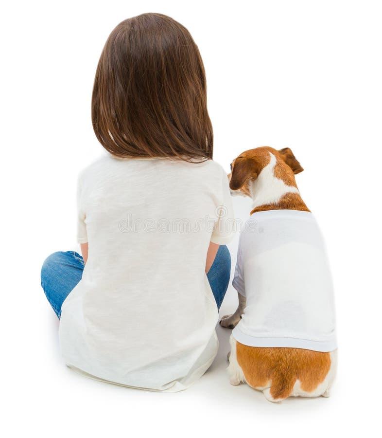 Baksidor av den lilla flickan för vänner och hennes hunden som ner sitter i samma vit T-tröja royaltyfri bild