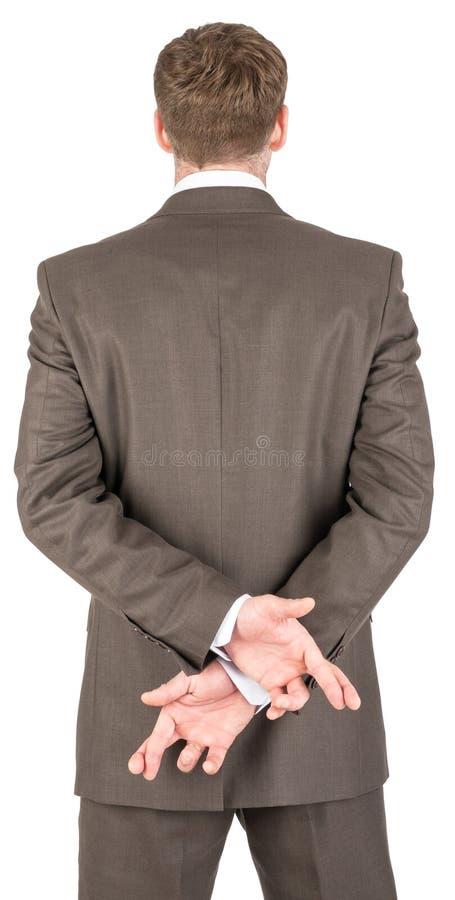 baksidt bak hans affärsmancrossingfingrar royaltyfria foton