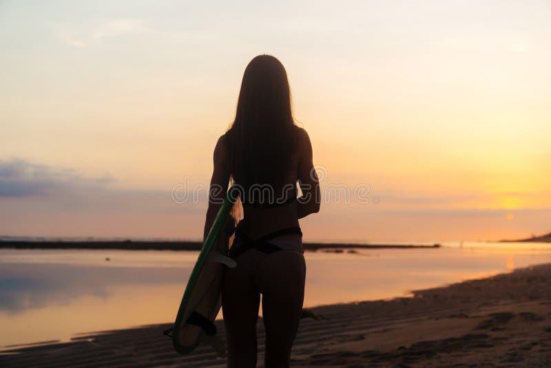 Baksiktskontur av surfareflickan med bränningbrädet på stranden på solnedgången royaltyfri fotografi