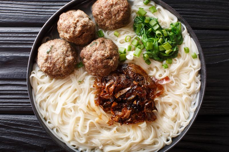 Bakso meatballs with noodles, fried onions, greens and broth close-up on a plate. horizontal top view royalty free stock photo