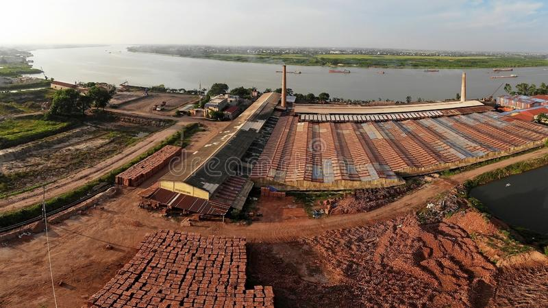 Baksteenfabriek die op de rivierbank wordt gevestigd stock afbeelding