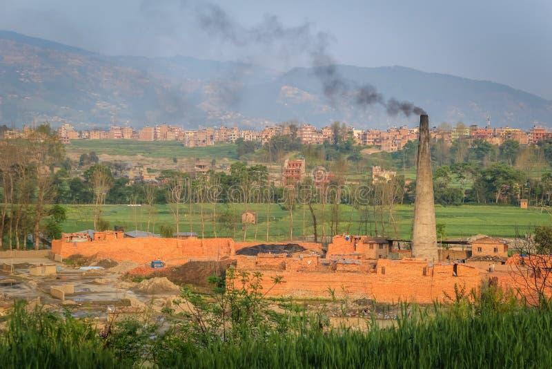 Baksteenfabriek met schoorsteen en zwarte rook stock foto