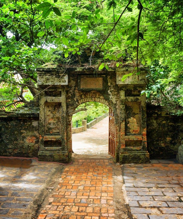 Baksteengang aan oude steenpoort die in tropische tuin leiden stock foto
