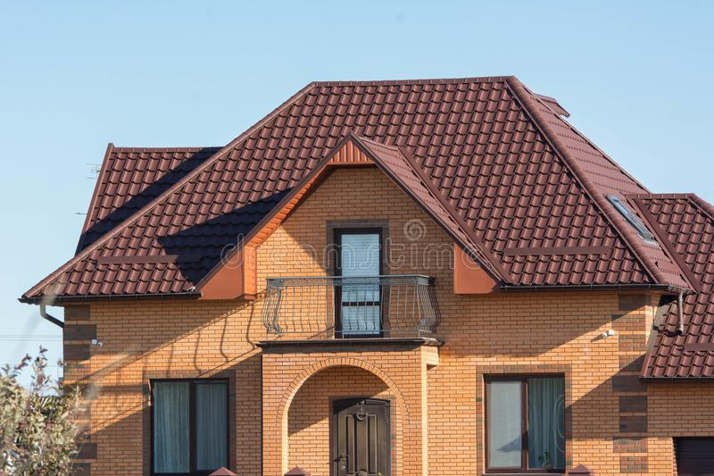 Baksteenhuis met balkon, dak op verscheidene niveaus en zolderdakramen royalty-vrije stock afbeelding