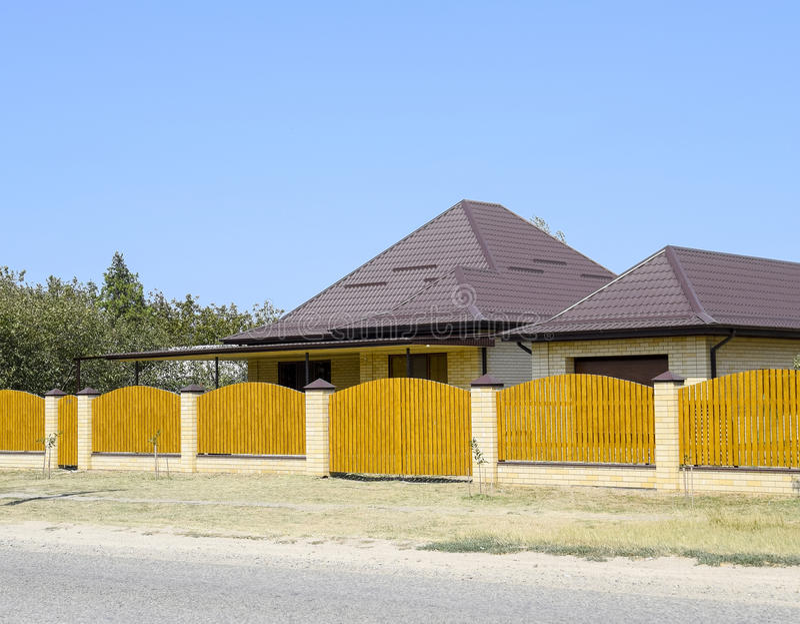 Baksteenhuis met het golfdak van het metaalprofiel en houten omheining Mooie mening van de voorgevel Stijl van ontwerp royalty-vrije stock afbeeldingen