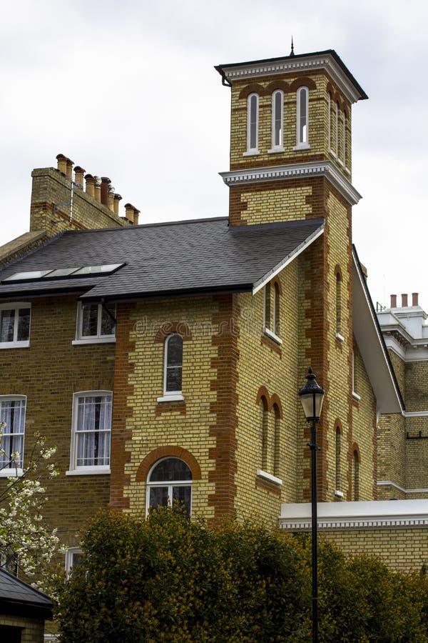 Baksteenhuis met witte vensters en een toren op een stil gebied van centraal Londen Lantaarnpaal, bloeiende bomen royalty-vrije stock foto