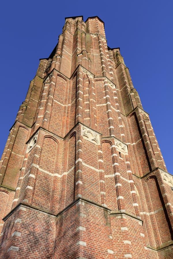 Baksteentoren van Saint Michelkerk tegen blauwe hemel, Rafels, Vlaanderen, België stock afbeeldingen