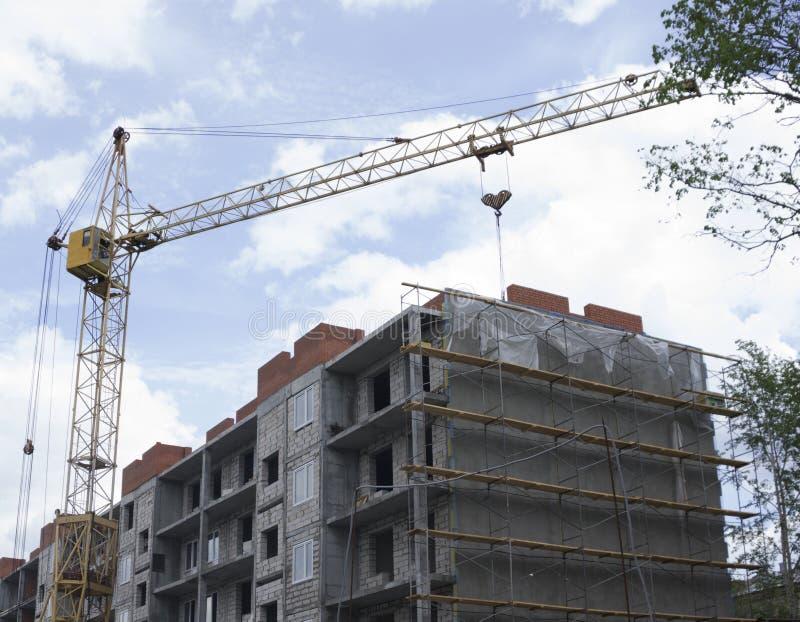 Bakstenen die in openlucht leggen Bouwkranen en high-rise de bouw in aanbouw tegen blauwe hemel stock afbeelding
