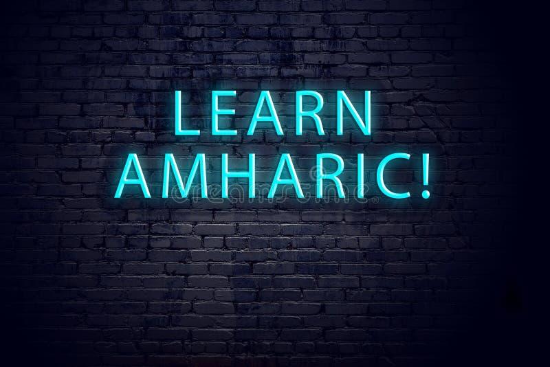 Bakstenen muur en neonteken met inschrijving Amharic concept het leren royalty-vrije stock fotografie
