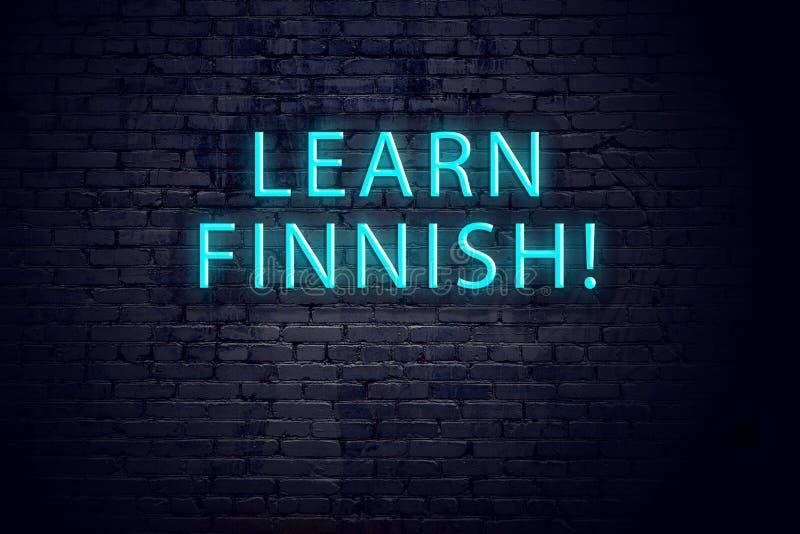 Bakstenen muur en neonteken met inschrijving Concept het leren van Finnen stock afbeeldingen