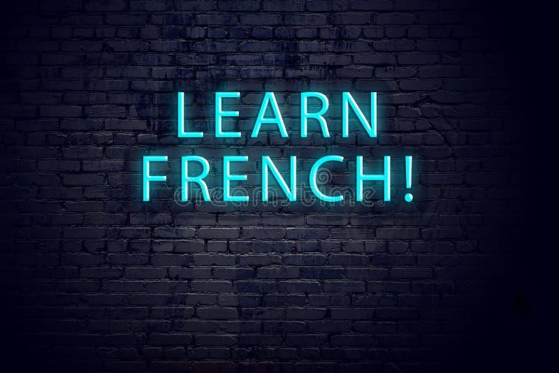 Bakstenen muur en neonteken met inschrijving Concept het leren van het Frans stock fotografie