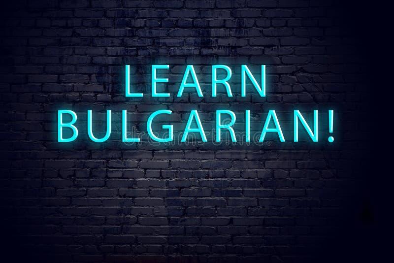 Bakstenen muur en neonteken met inschrijving Concept lerende Bulgaar royalty-vrije stock fotografie