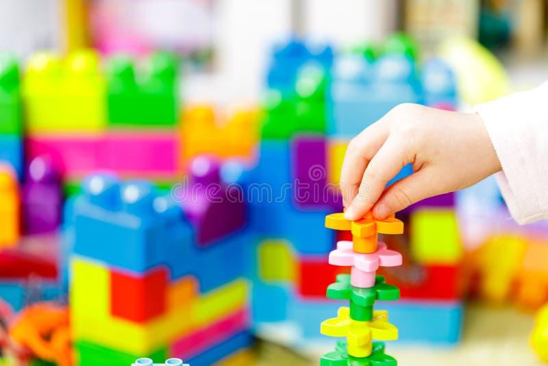 Bakstenen van de kinderen de plastic kleur met kinderenhand Sluit omhoog stock afbeeldingen