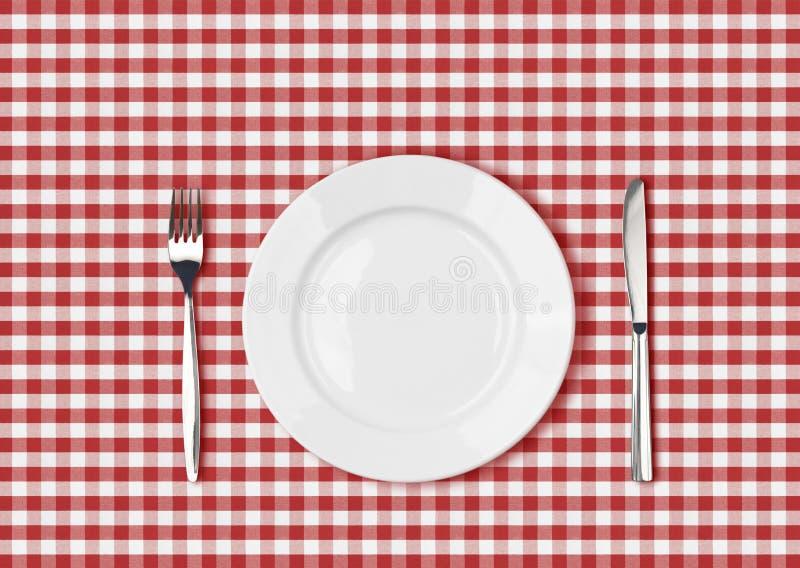 Baktala, den vita plattan och gaffeln på den röda picknicktabelltorkduken arkivbilder