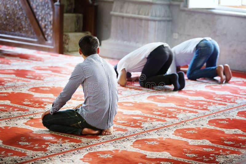 BAKU, AZERBAIJÃO - 17 de julho de 2015: Um homem muçulmano não identificado reza na mesquita de Juma foto de stock royalty free