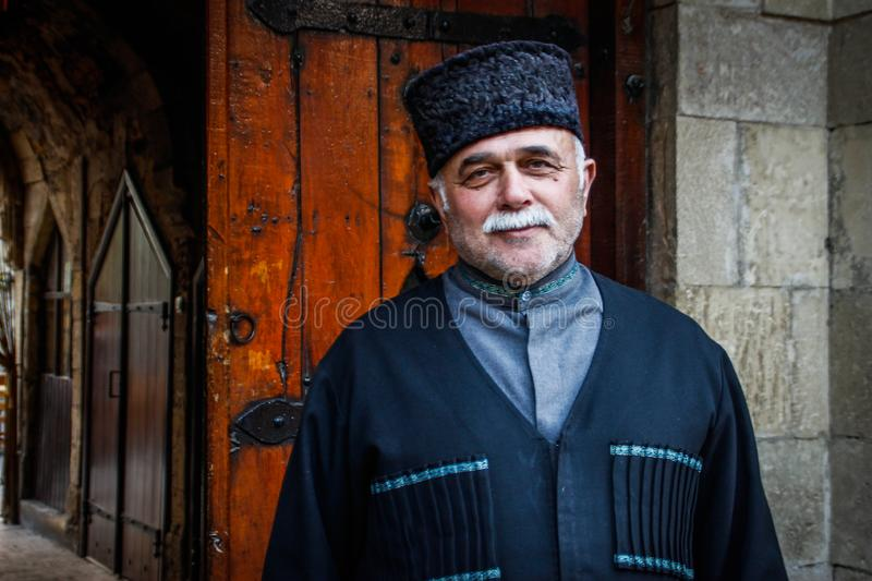 Handsome elderly man smiles in national Azeri costume, hat and gray mustache stock photography